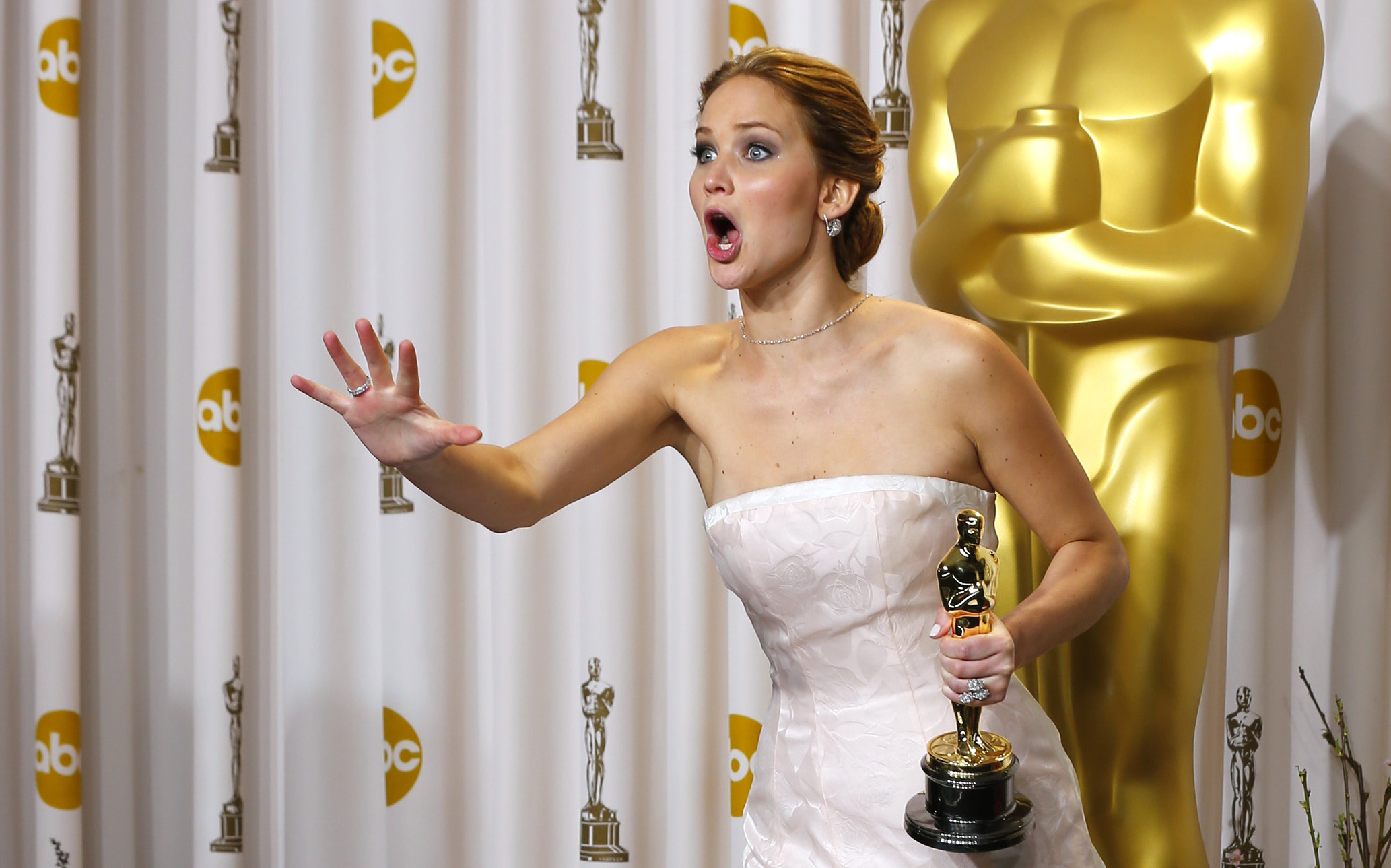 """Jennifer Lawrence, best actress winner for her role in """"Silver Linings Playbook,"""" reacts after photographers made a picture of her making an obscene gesture as she took the stage in the photo room with her Oscar at the 85th Academy Awards in Hollywood, California February 24, 2013    REUTERS/Mike Blake (UNITED STATES  - Tags: ENTERTAINMENT)  (OSCARS-BACKSTAGE) - RTR3E9DL"""